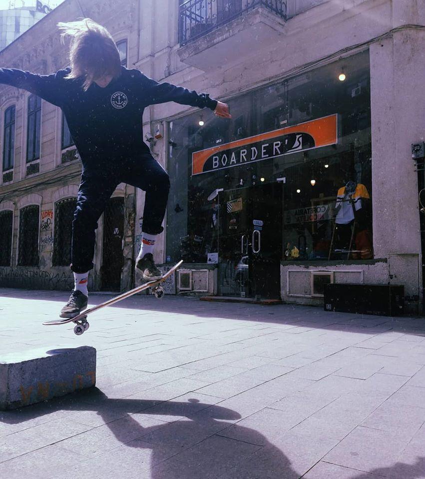 Skater incepator executa o schema cu skateboardul in fata magaziunlui Boarders din strada Domnița Anastasia nr.9
